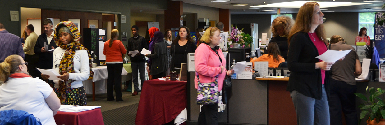 People Walking Around The CareerCenter Talking With Employers At Job Fair Exhibits